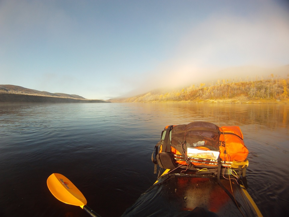 Figure 27: Paddling down the Tana River in extreme Northern Norway on a frosty late september morning - my river map is attached to my backpack on the bow of my raft.